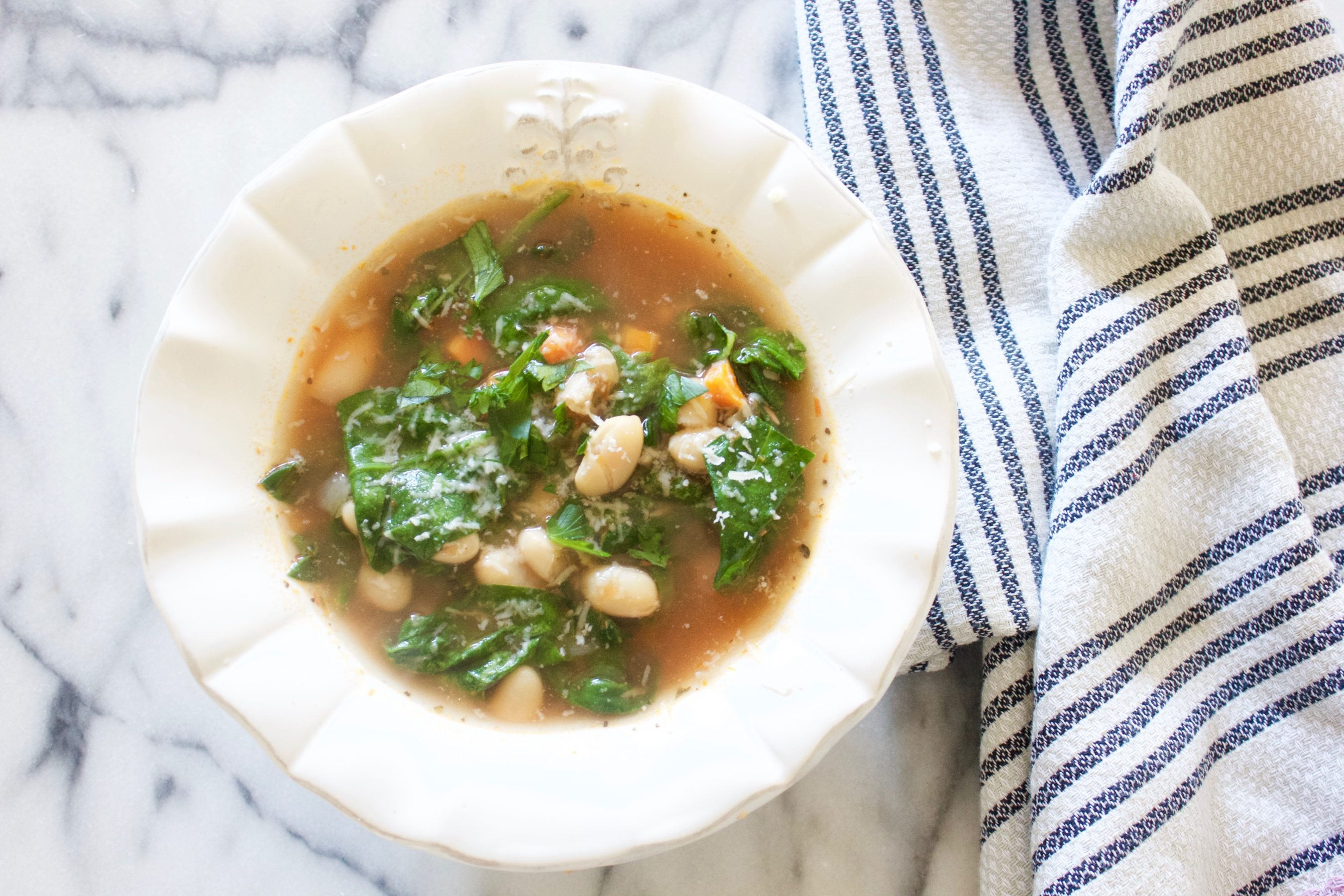 Soup with white beans and spinach and carrots in a white bowl on a marble counter top