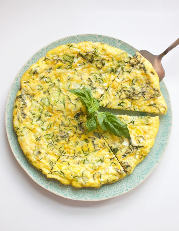 Frittata on w blue plate with a silver serving spatula and basil garnish