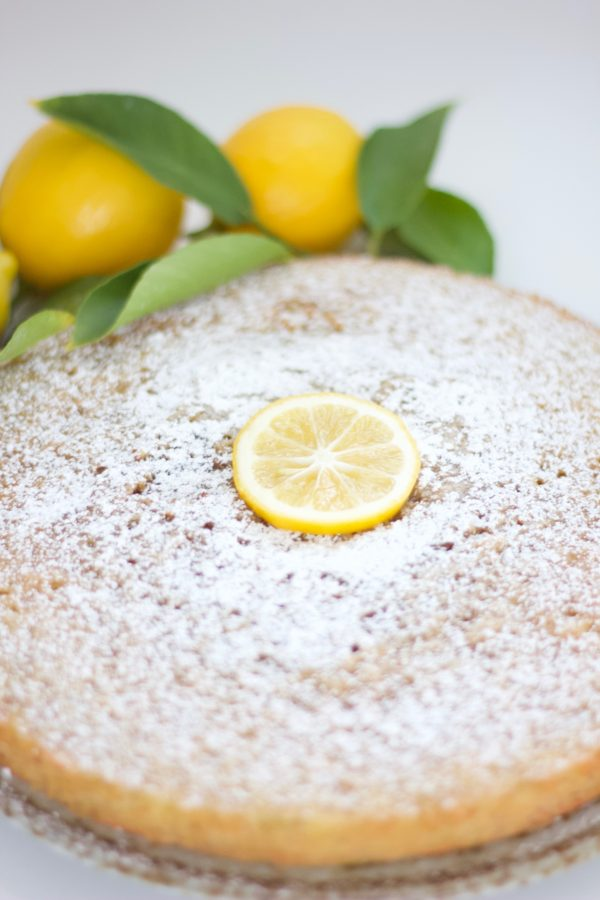 Lemon olive oil cake topped with powdered sugar and a slice of lemon and lemons with leaves in the background