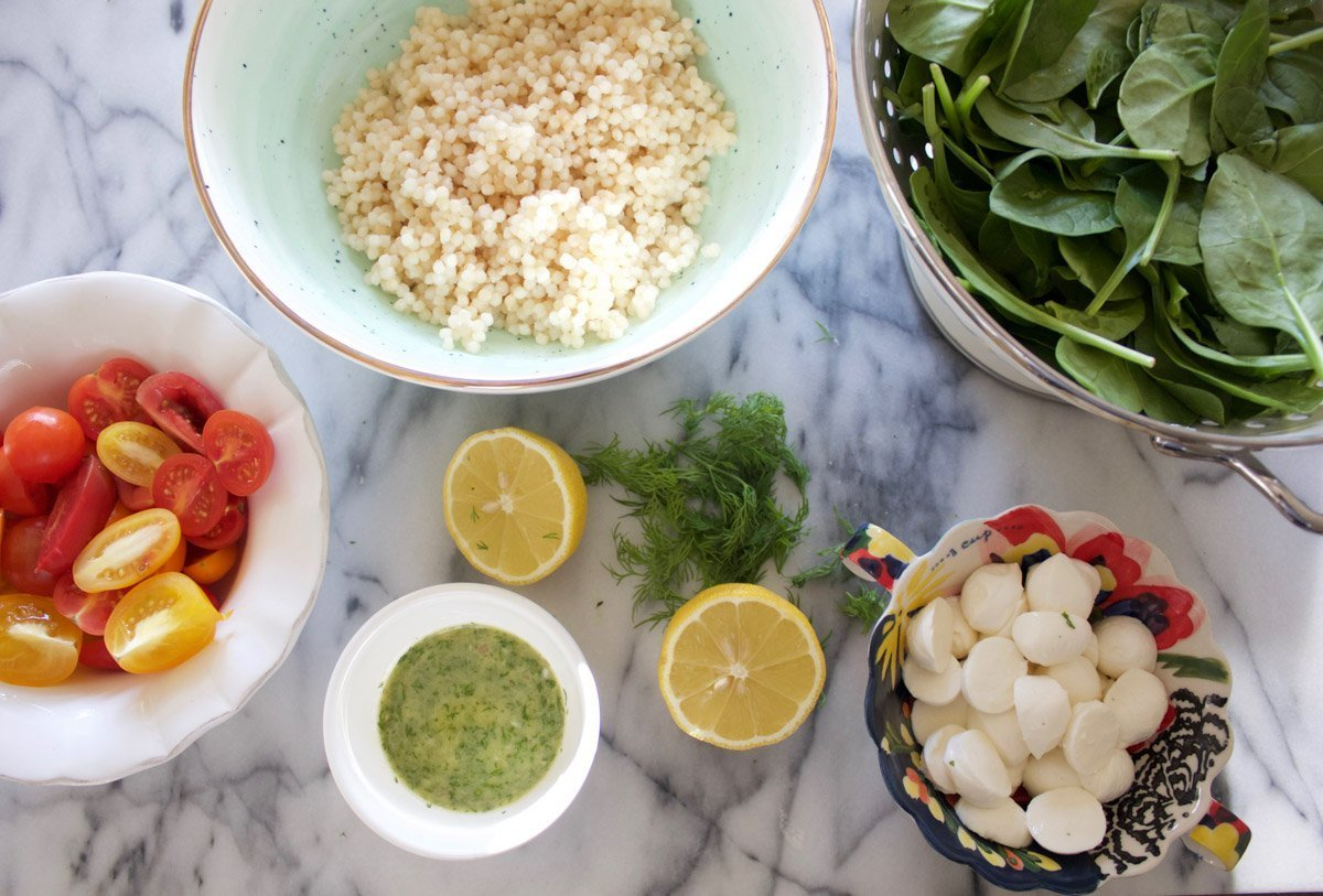 Chicken, Israeli Couscous, Spinach, Tomatoes, Fresh Mozzarella and Dill Vinaigrette in small bowls on a marble counter.