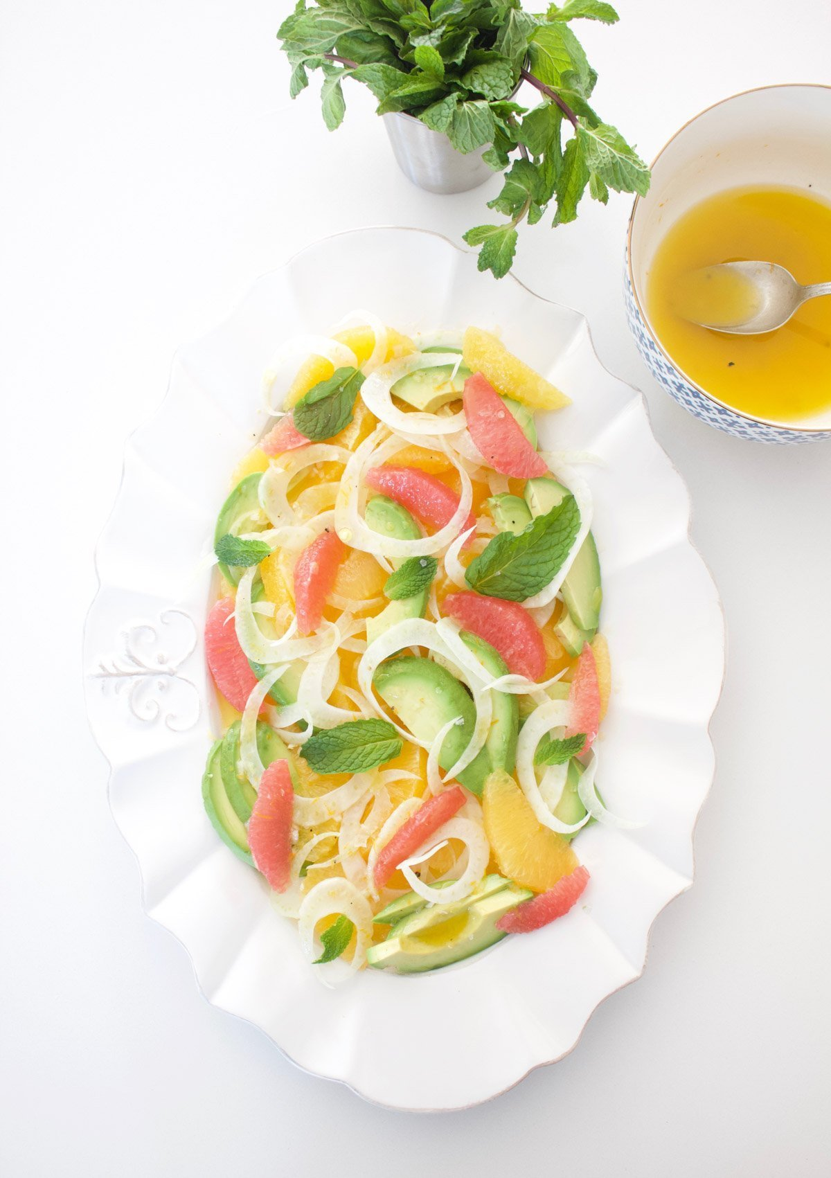Citrus and avocado salad with a bowl of dressing on the side