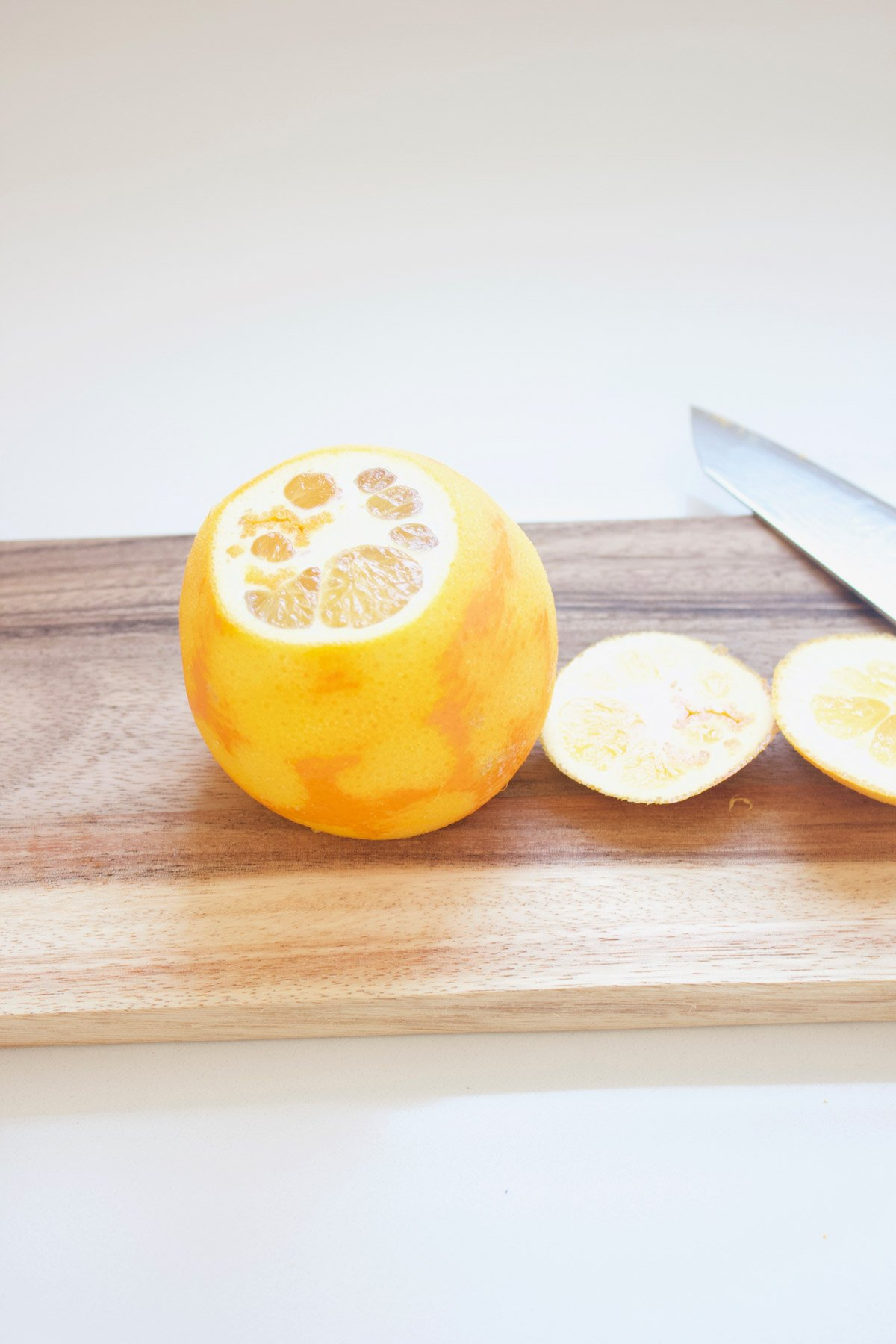 Orange with the end cut off on a cutting board.