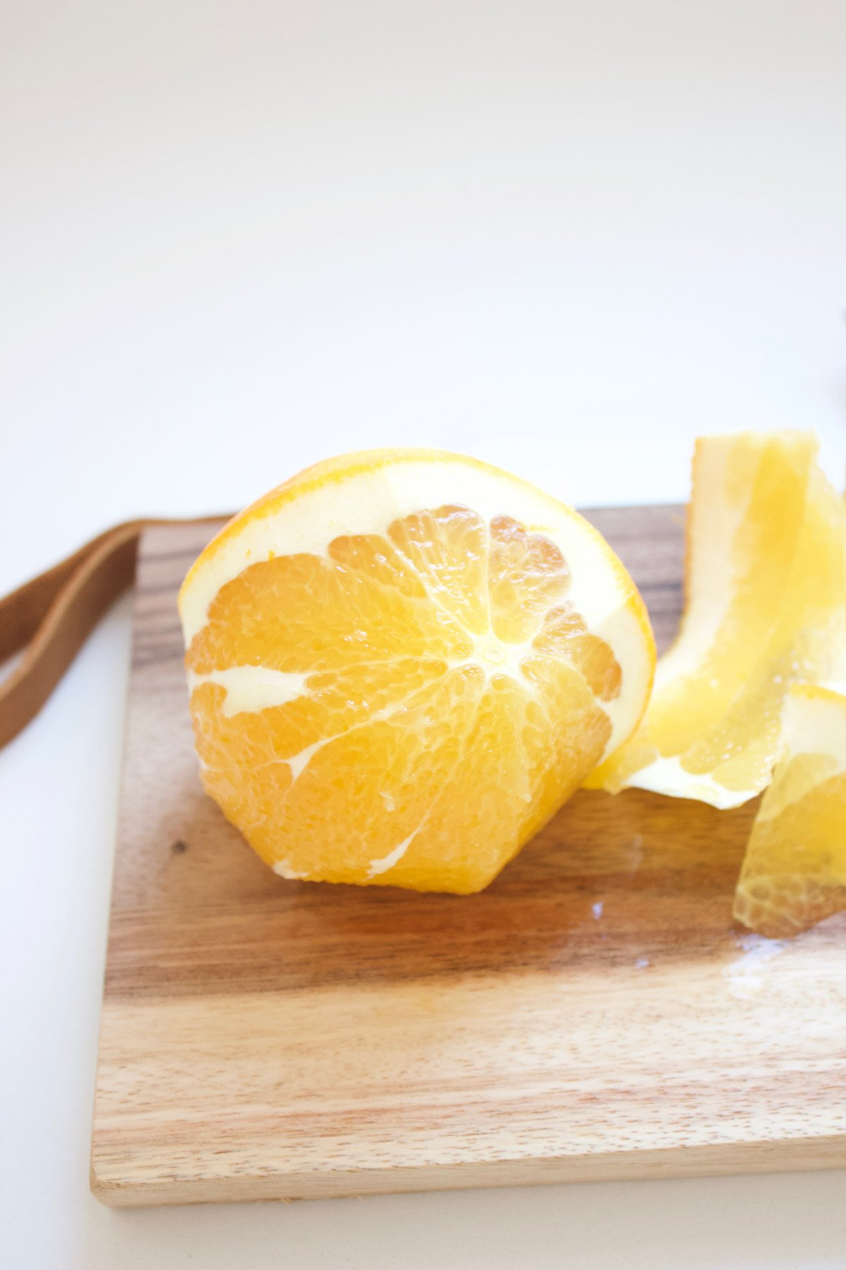 Peeled navel orange on a cutting board.