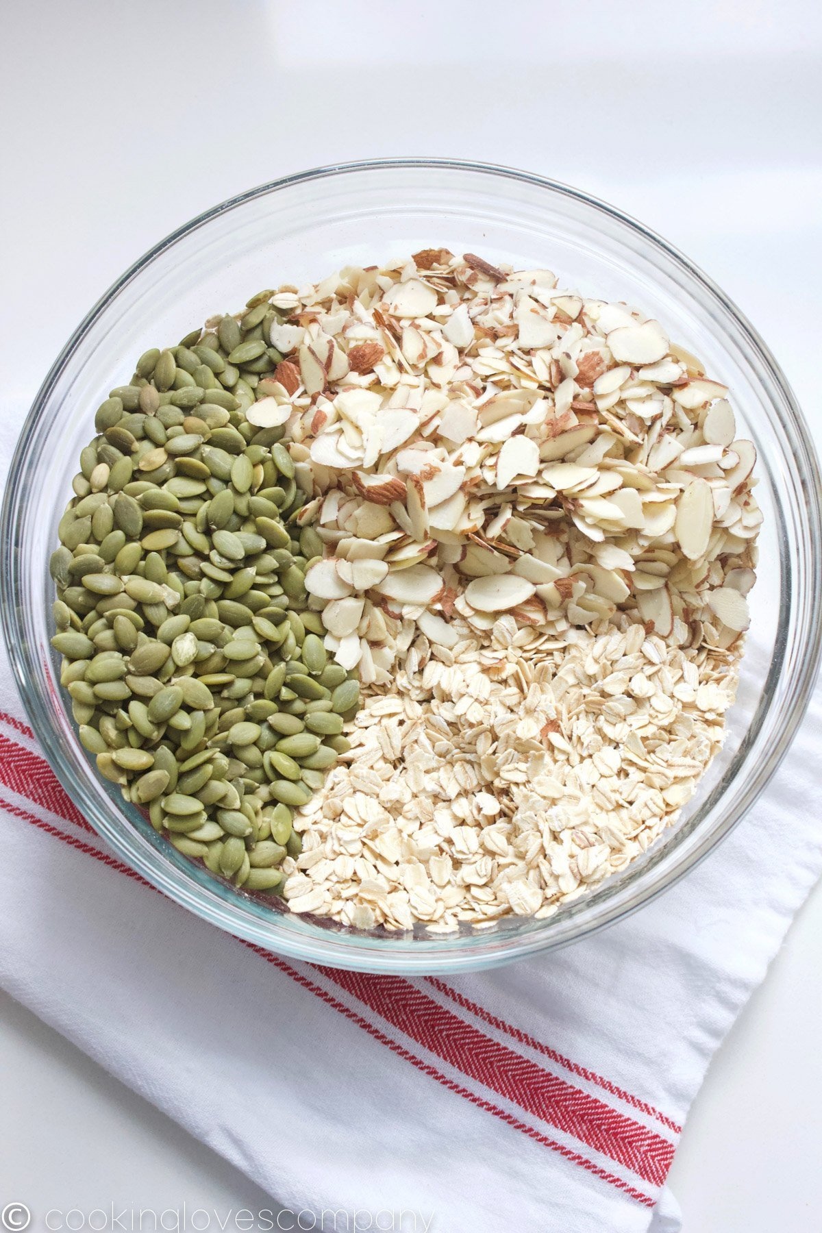 Pumpkin seeds, rolled oats and slivered almonds in a glass bowl on a counter