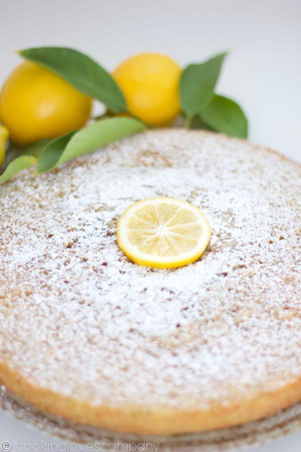 Lemon Olive Oil Cake on a platter with a few lemons as garnish