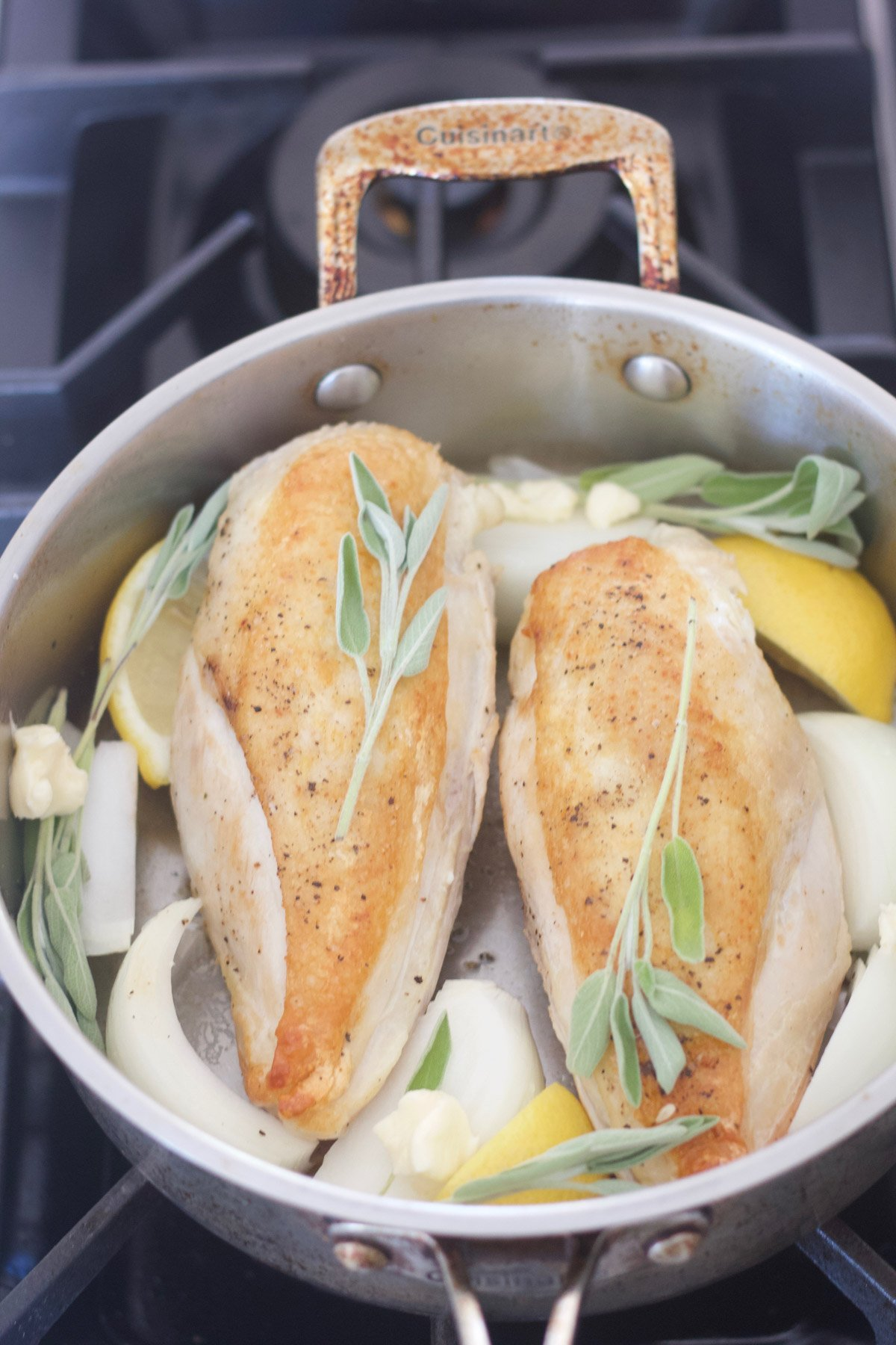 Two chicken breasts in a pan with onions and lemons and sage