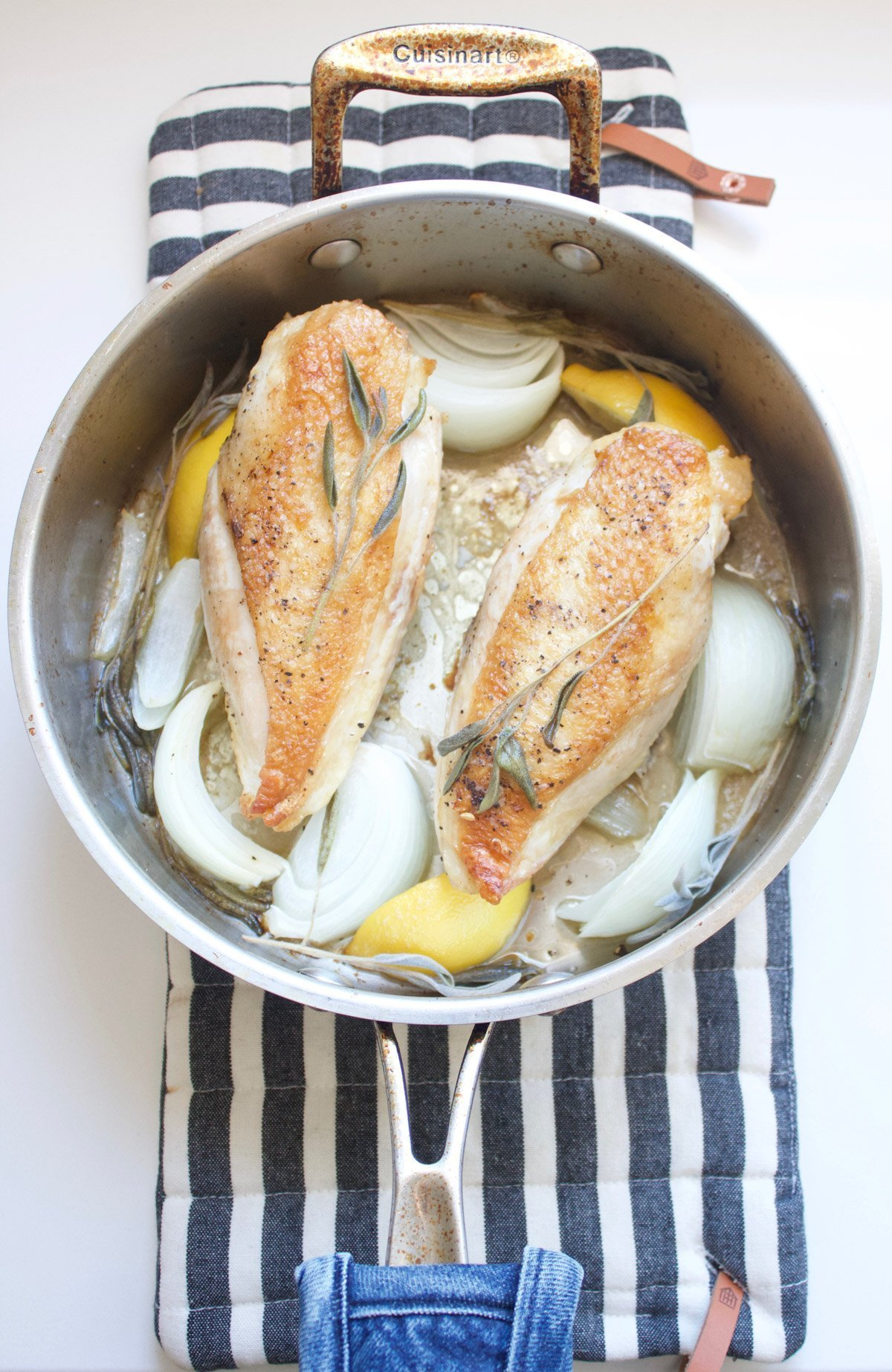 Cooked chicken breast in a pan with onions, lemon and sage
