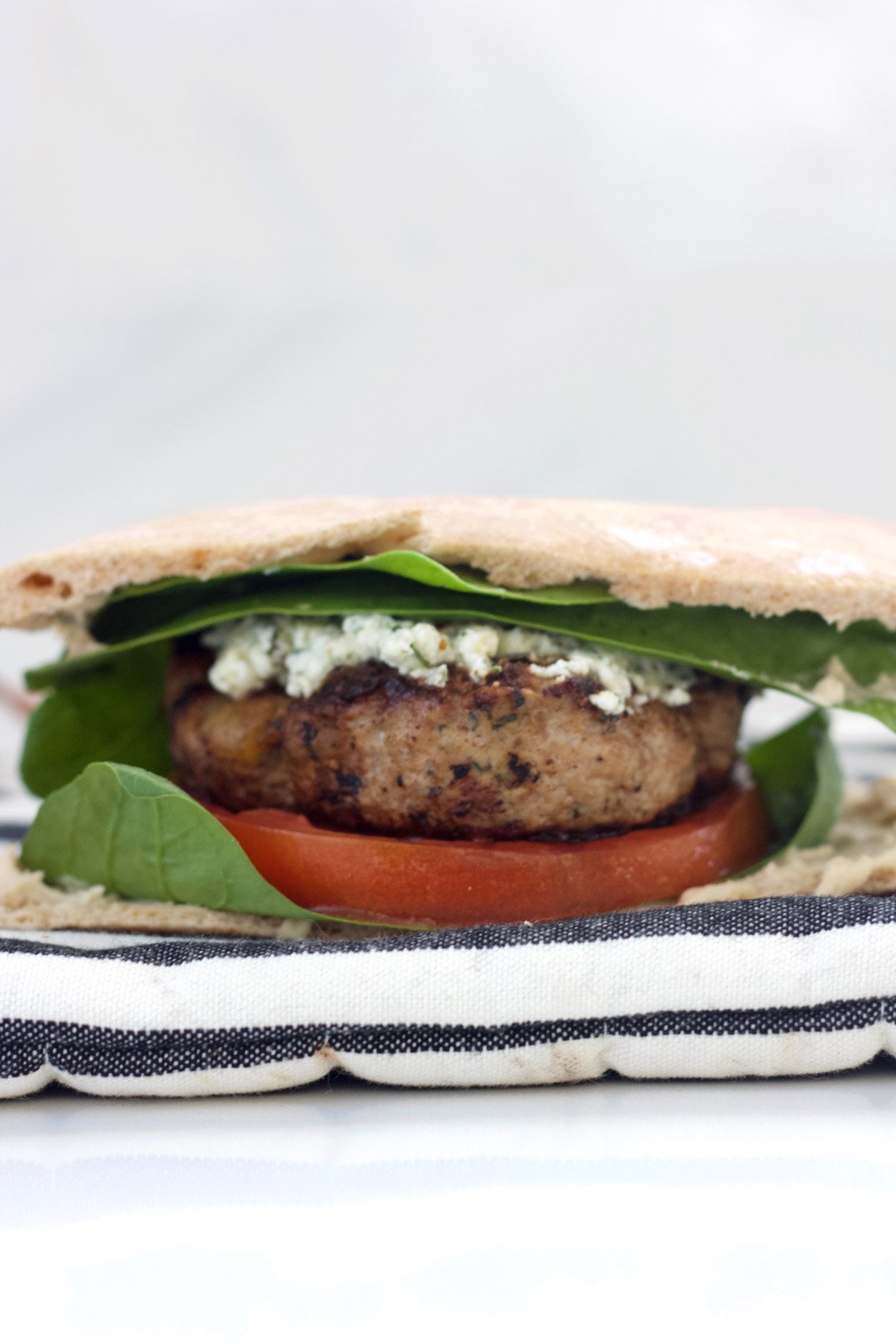 Turkey burger with herbed feta, spinach, tomato and hummus