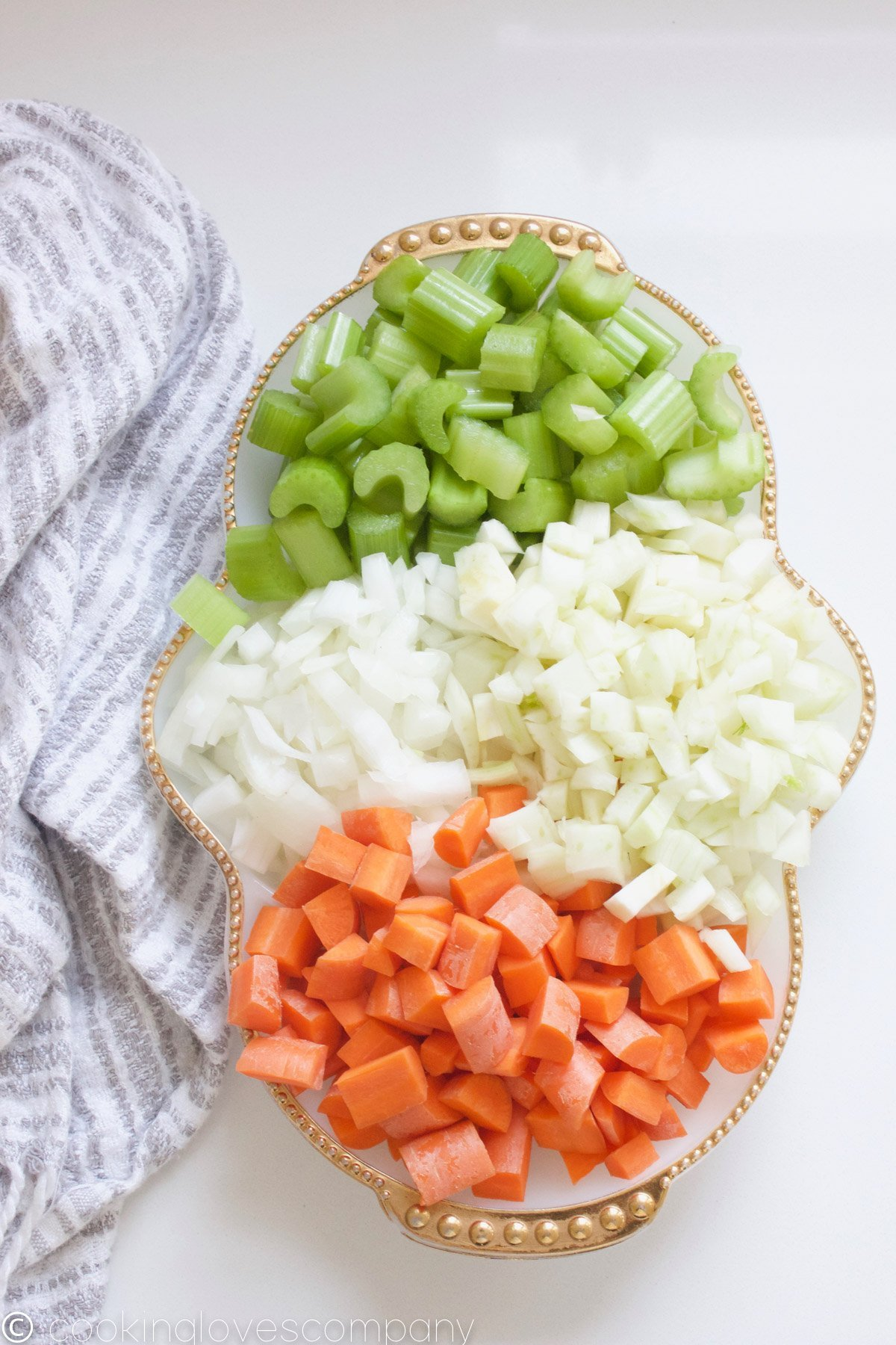 Chopped celery, carrots and onion on a platter with a grey and white towel