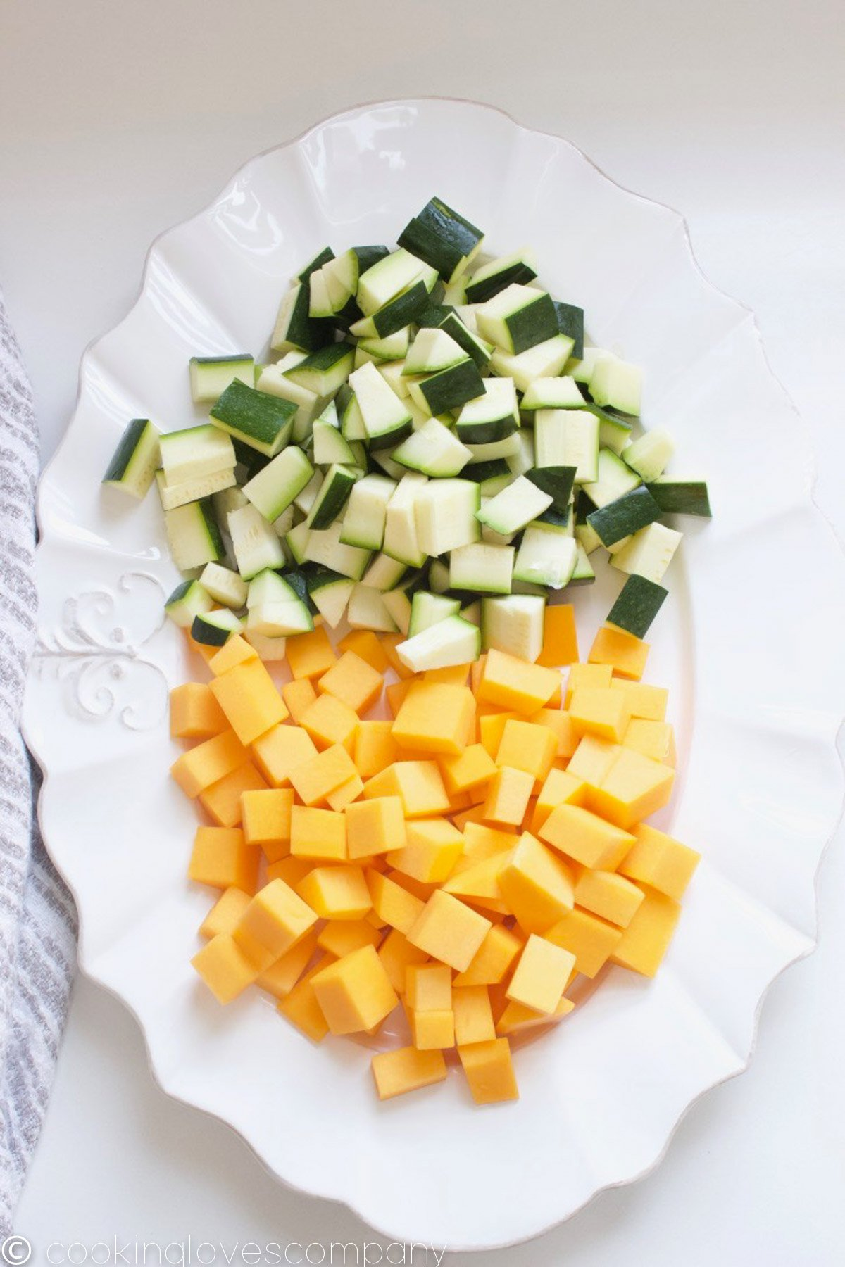 Cubed zucchini and butternut squash on a white platter