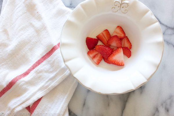 Sliced strawberries in a white bowl on a marble counter