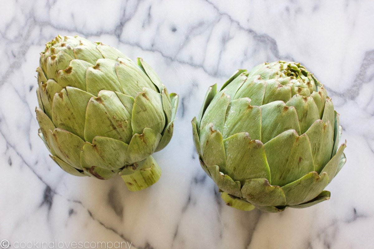 Two artichokes on a marble counter