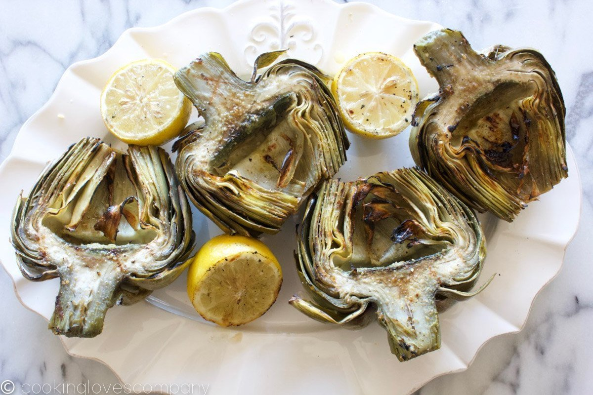 Four grilled artichoke halves and three grilled lemon halves on a white platter