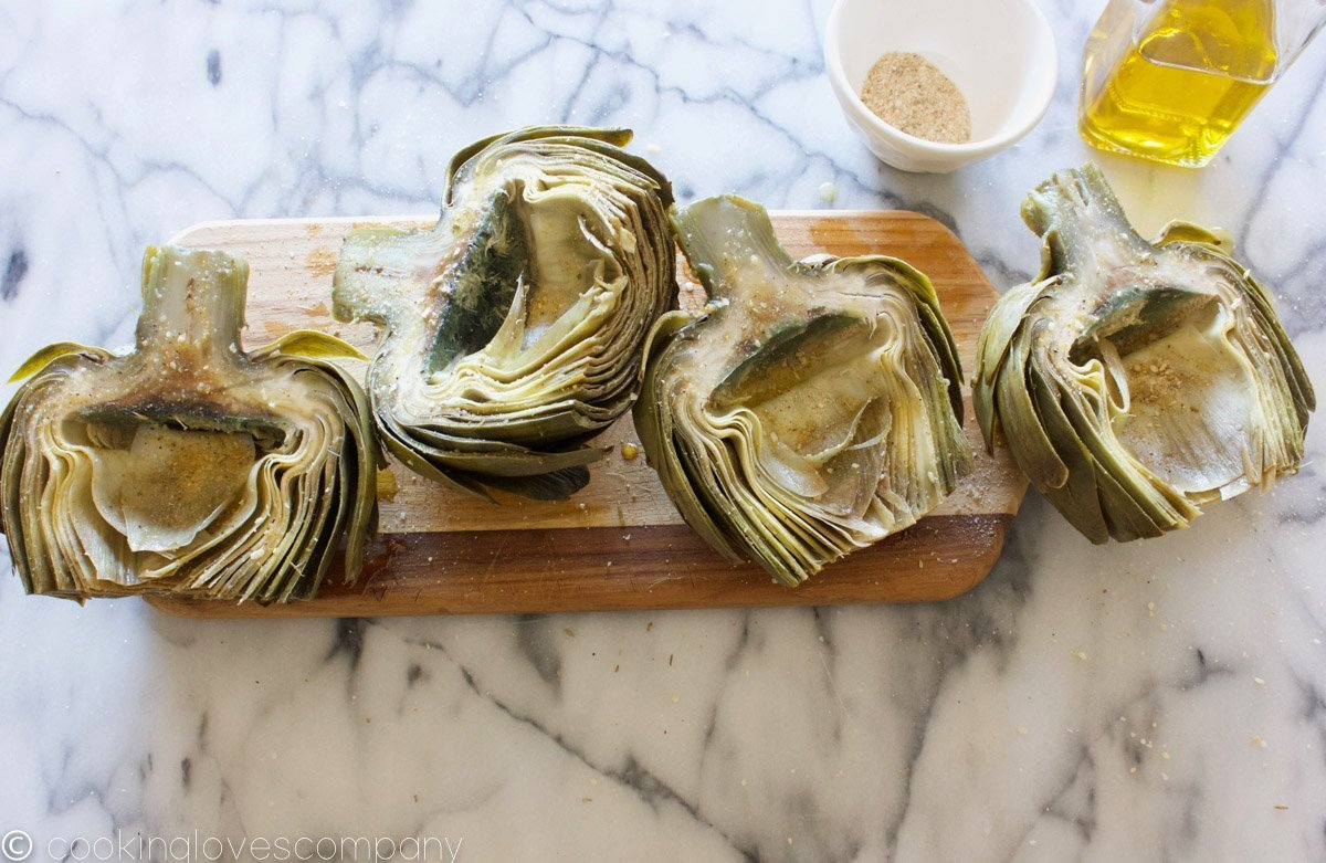 Four artichoke halves on a cutting board sprinkled with spices and olive oil