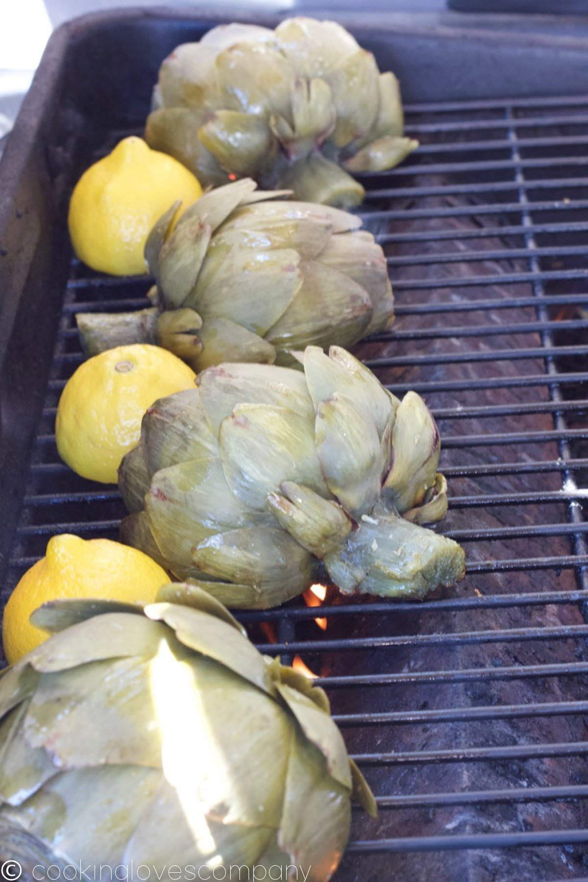 Four artichoke and lemon halves cut side down on a grill