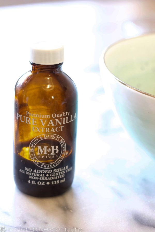 A close up shot of a bottle of pure vanilla extract on a marble counter top