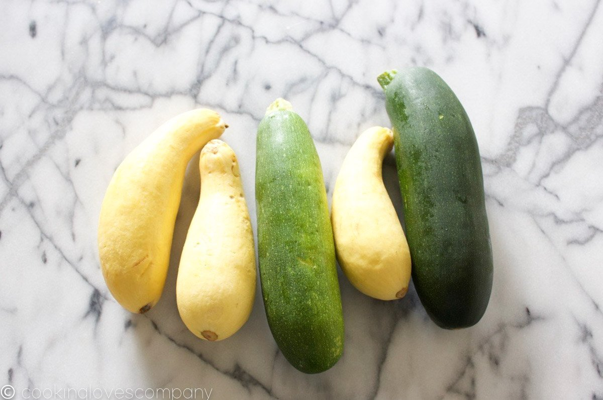 Yellow and green summer squash on a marble counter