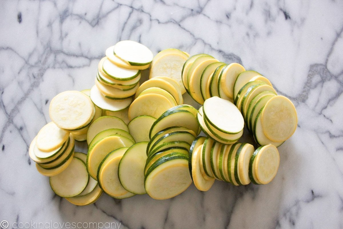 A pile of thinly sliced summer squash on a marble counter