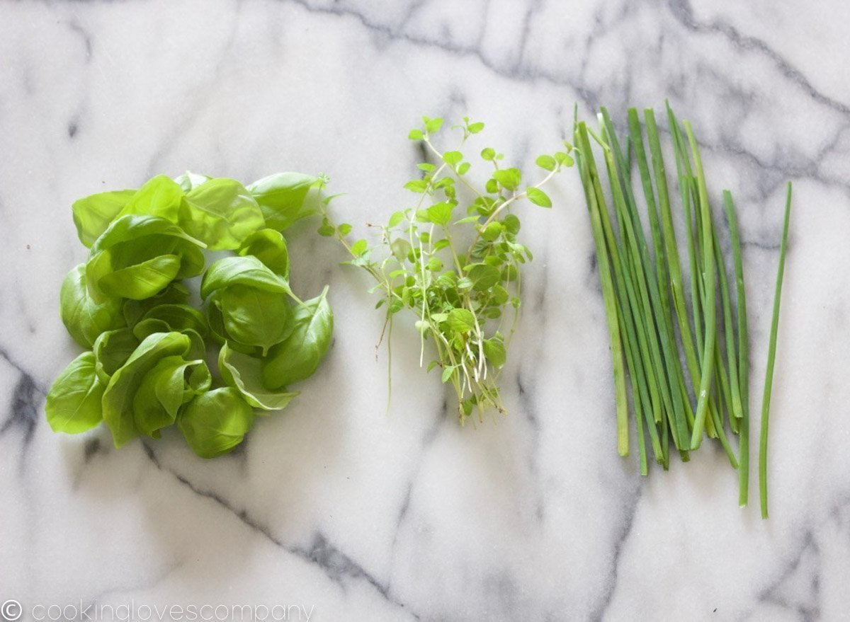 Three separate piles of herbs, basil, mint and chives on a marble counter