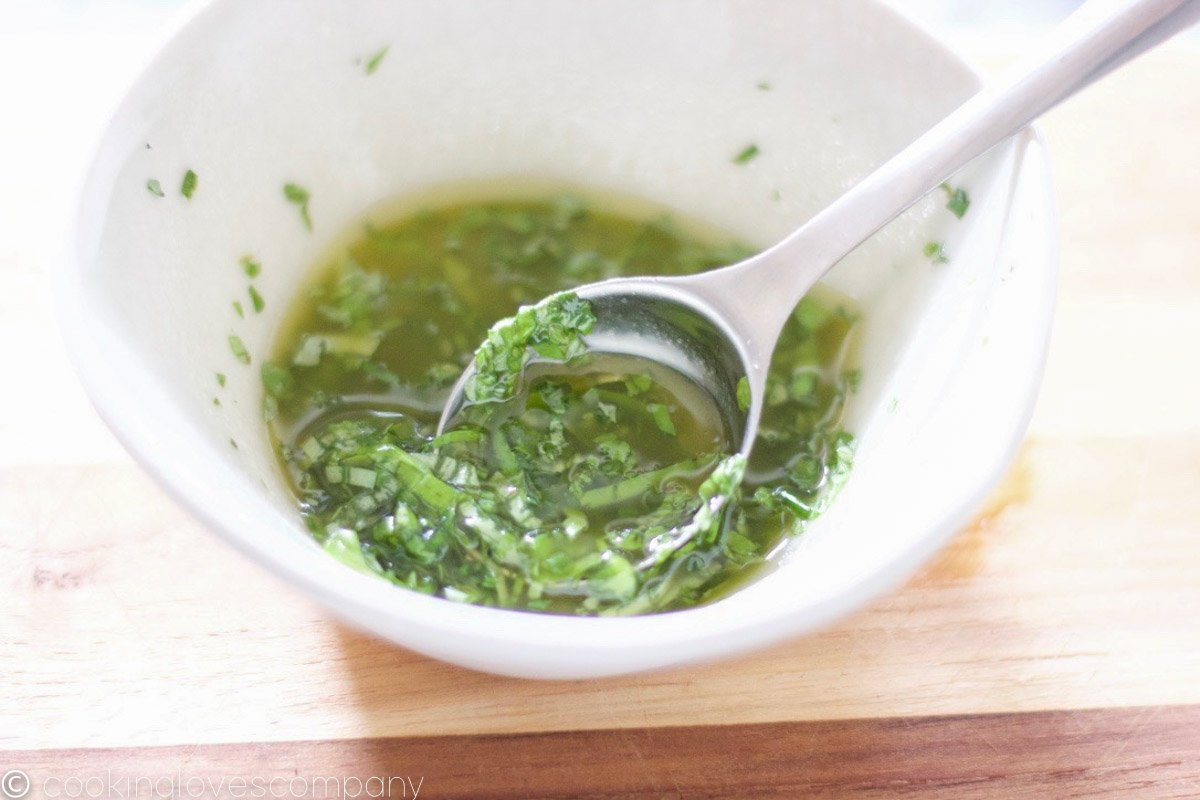 Herb vinaigrette in a small white bowl with a spoon