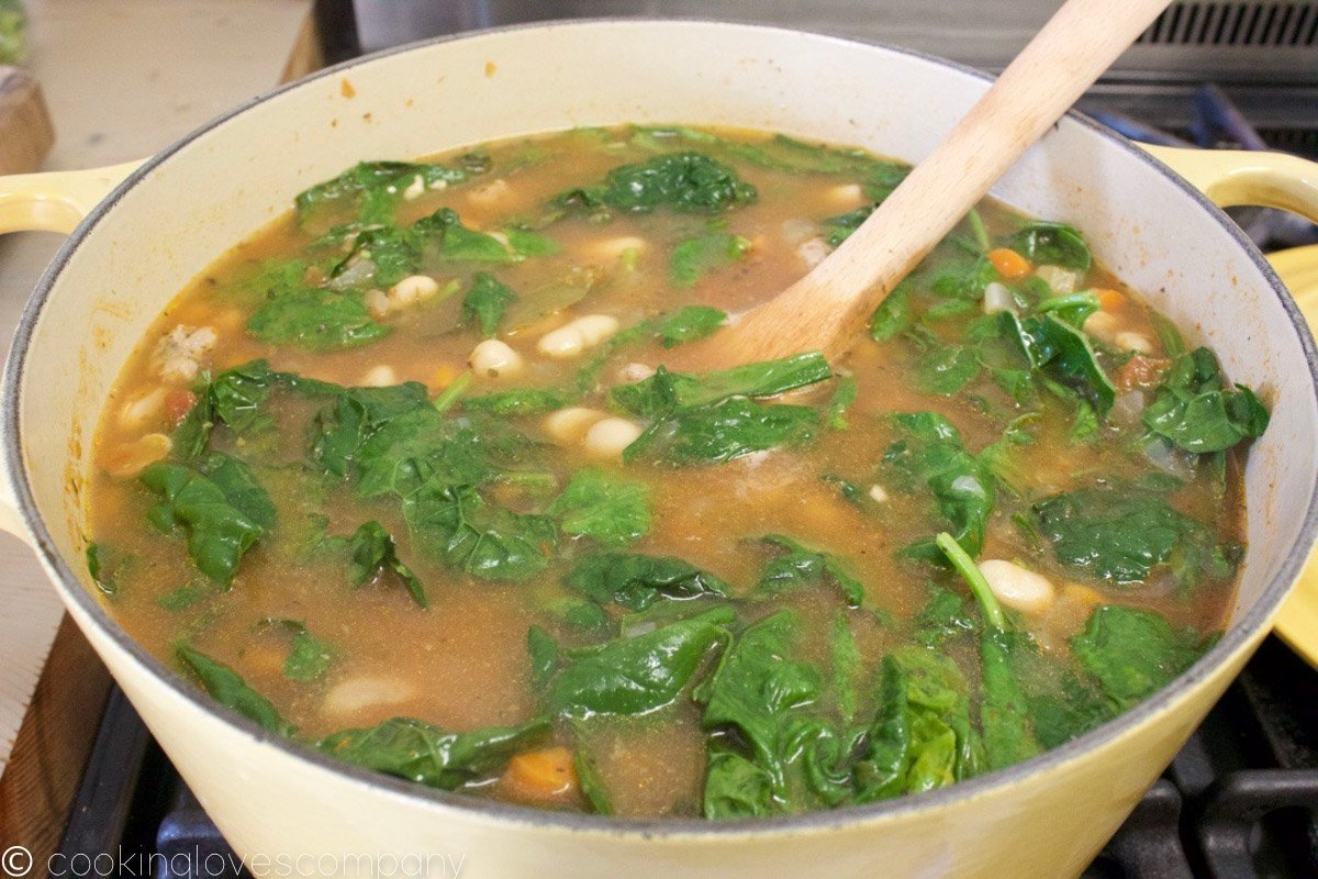 A pot of Italian Wedding Soup with white beans and spinach in a dutch oven on a stovetop