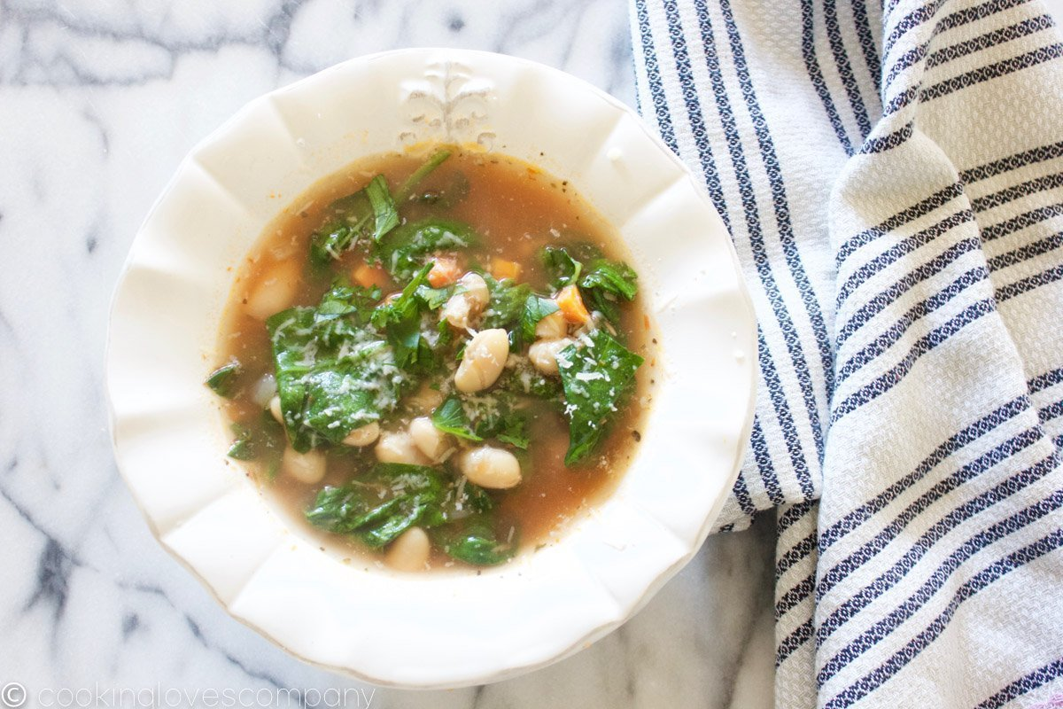 A bowl of Italian Wedding Soup with white beans and spinach in a white bowl on a marble counter