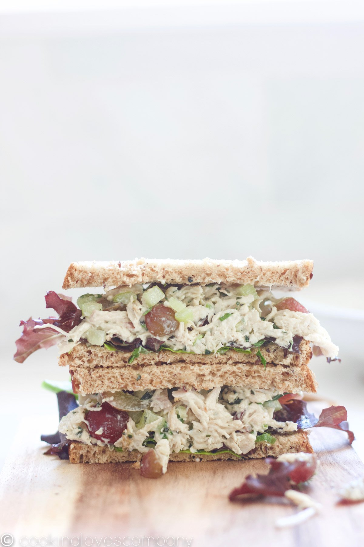 A tarragon chicken salad sandwich sliced in half and stacked, sitting on a wooden cutting board.
