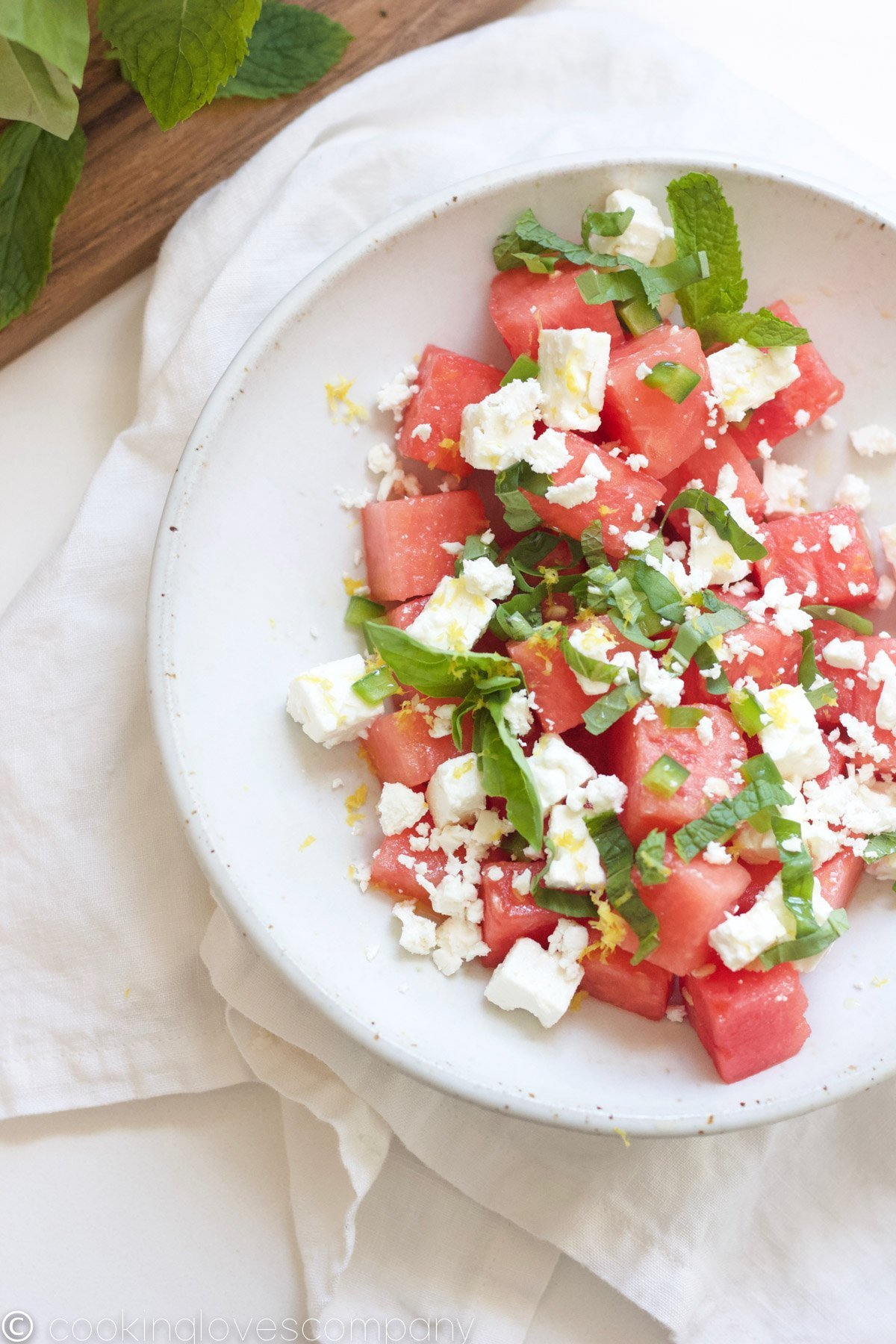 Overhead shot of a watermelon and feta salad with basil and mint in a bowl