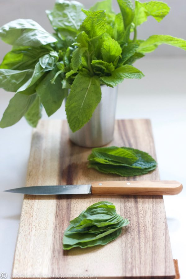 Basil and Mint in a small stainless steel cup on a cutting board