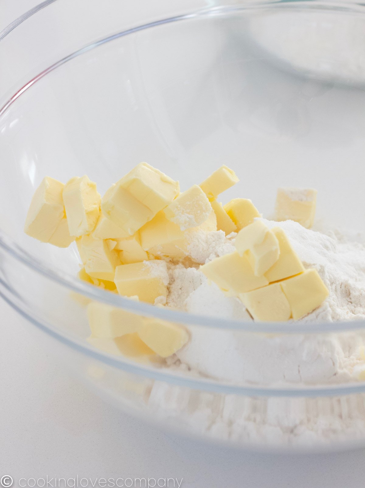 Close up of a glass mixing bowl with cubed butter, sugar and flour