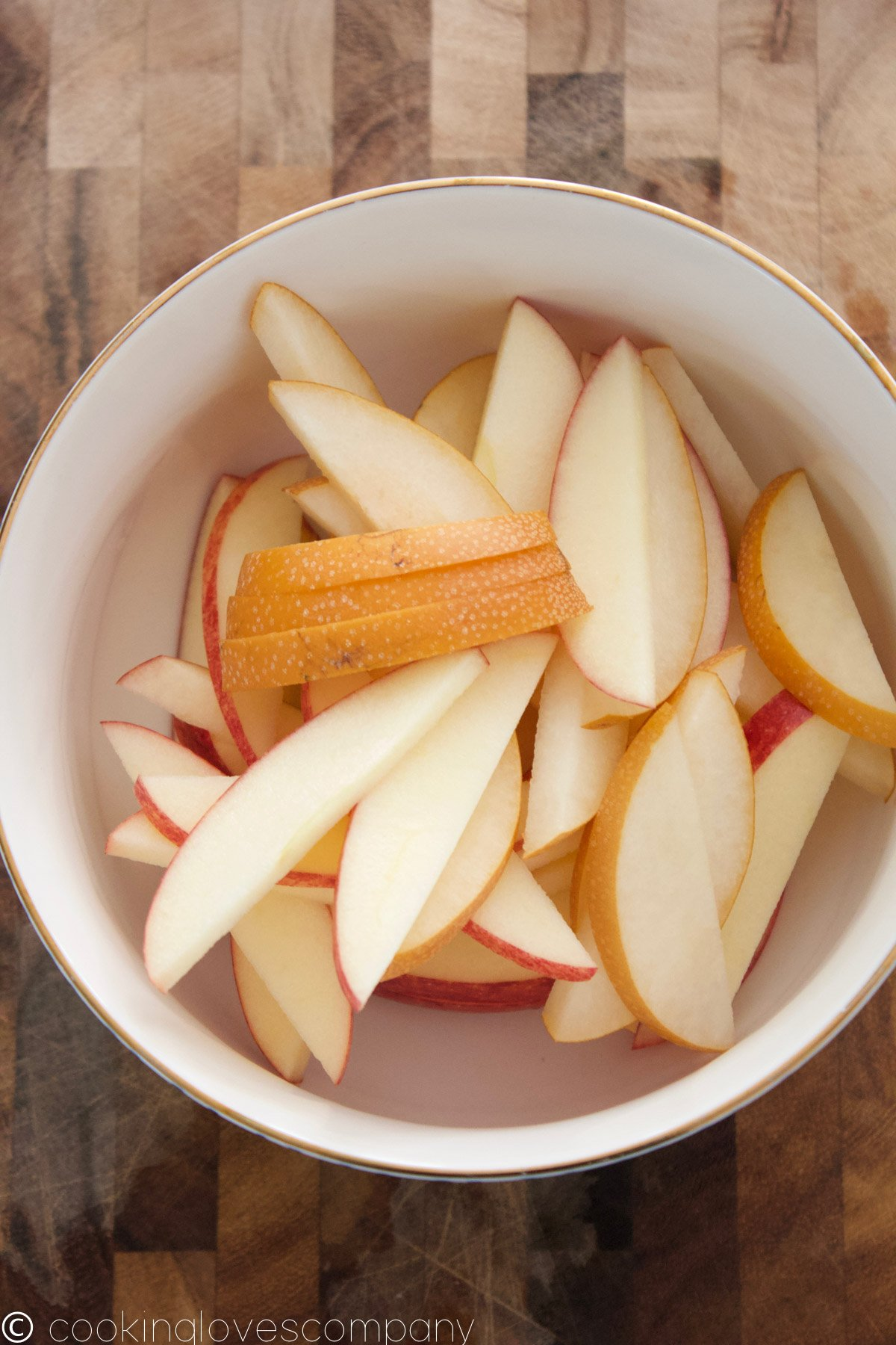 A white bowl with a gold rim on a wooden cutting board filled with sliced apples and pears
