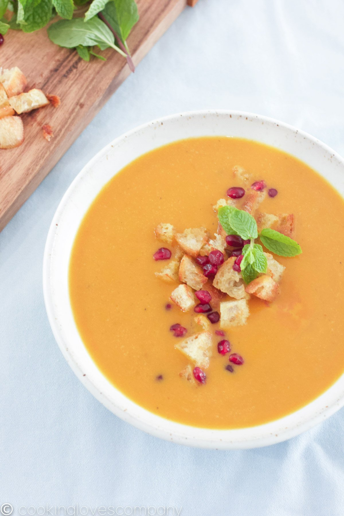 Bowl of pumpkin curry soup with croutons and pomegranate seeds
