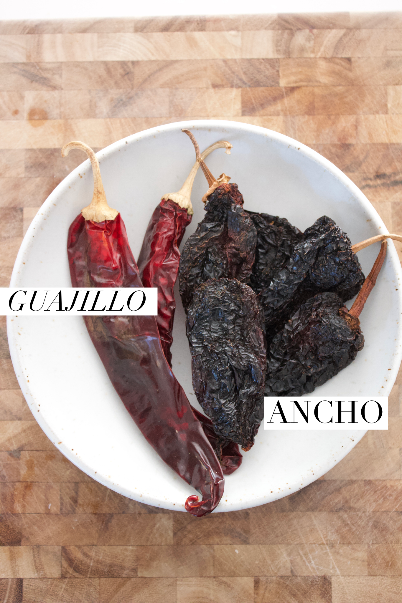 Dried guajillo and ancho chiles in a bowl on a cutting board