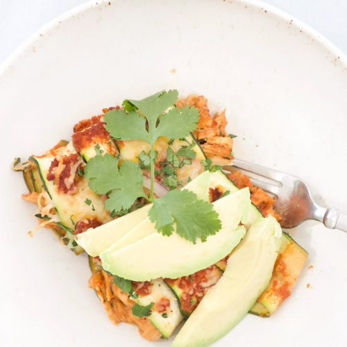 2 Zucchini Enchiladas with a sprig of cilantro and sliced avocado in a bowl with a fork